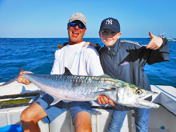 Capt. Dan Barry holding Kingfish caught by young angler on a deep sea fishing charter.