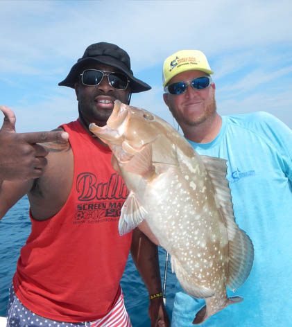 Two men holding a Grouper caught on their deep sea fishing charter off the shore of St. Petersburg, FL.