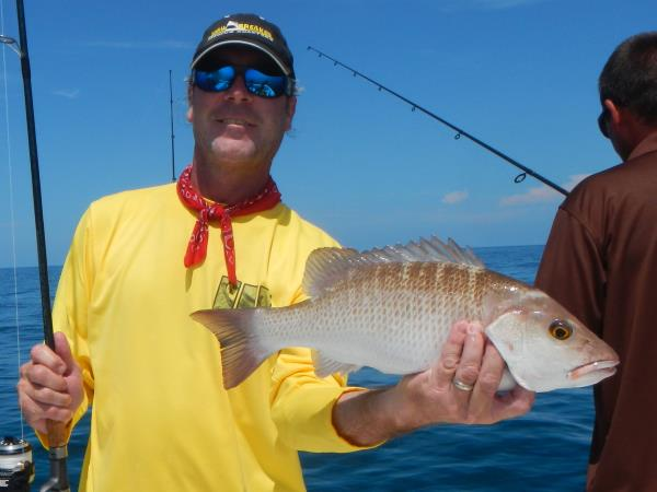 Captain Dan Barry holding fresh Grouper and Tuna caught on The Jawbreaker.